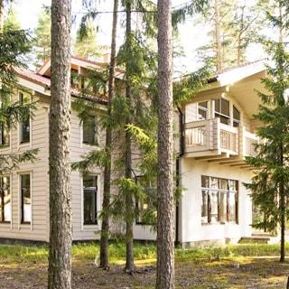 На летнем фото: двухэтажный коттедж из профилированного бруса, с балконом и скатной крышей, кровля - черепица, большие окна, участок - газон, на участке - сосны и ели