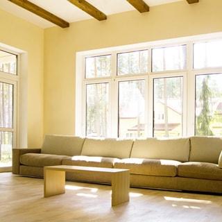 На фото: большое светлое помещние жилой комнаты - гостиной, большое четырехстворчатое окно, стеклянная дверь выхода на крыльцо, большой мягкий диван у окна, пред ним - журнальный столик, стены и потолки окрашены, полы - ламинат