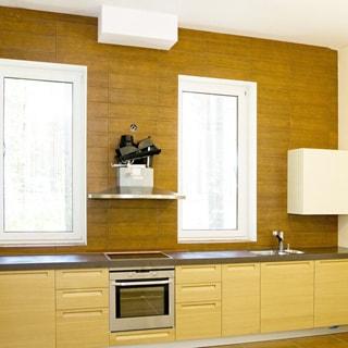 На фото: часть помещения кухни, два окна, вдоль всей стены встроенная кухонная мебель (тумбы-столы) с общей столешницей, в середине - электрическая варочная поверхность, над ней - вытяжка, под ней - духовой шкаф, правее - металлическая мойка со смесителем, окна - стеклопакеты, полы и стена - плитка, потолок - окрашен в белый цвет