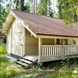 На летнем фото: часть фасада одноэтажного деревянного дома с крыльцом и скатной крышей, окна - стеклопакеты, кровля - черепица, перед домом - газон, на участке - хвойные деревья