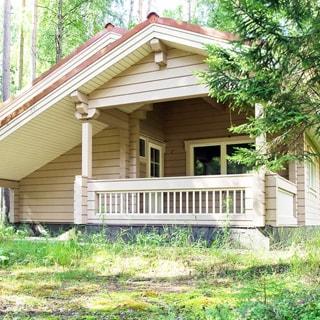 На летнем фото: одноэтажный деревянный дом с террасой и скатной кровлей, окна и входная дверь - стеклопакеты, перед домом - газон, на участке - хвойные деревья