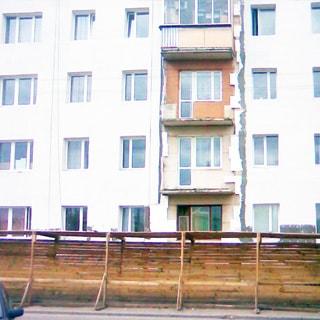 На фото: часть фасада многоэтажного (в кадре видны первые четыре этажа) многоквартирного жилого дома, на фасаде производятся ремонтные работы, на пешеходном тротуаре установлено защитное деревянное ограждение для пешеходов