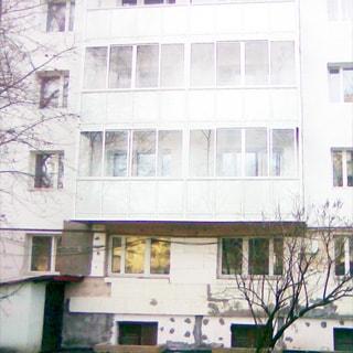 На фото: часть фасада многоэтажного (в кадре видны первые четыре этажа) многоквартирного жилого дома, на фасаде следы ремонтных работ, балконы - со второго этажа, застеклены, перед домом - кусты и деревья