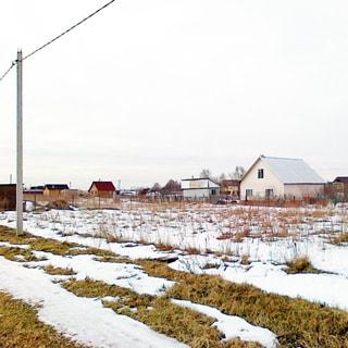 На зимнем фото: вид на земельный участок со стороны проселочной дороги, участок - ровный, пустой, не обработанный, без посадок и строений, не огорожен, перед участком вдоль дороги - бетонный столб воздушной линии электропередач, за участком - садовые дома и постройки соседних участков
