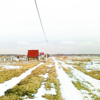 На зимнем фото: граница территории малоэтажной застройки, по границе - проселочная дорога, слева вдоль дороги - воздушная линия электропередач на железобетонных столбах, справа от дороги - чистое поле без построек и сооружений, на дальнем плане по дороге - продолжение малоэтажной застройки