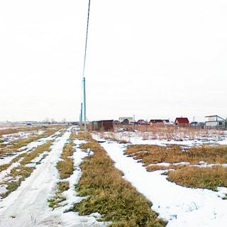 На зимнем фото: граница территории малоэтажной застройки, по границе - проселочная дорога, справа вдоль дороги - воздушная линия электропередач на железобетонных столбах, слева от дороги - чистое поле без построек и сооружений