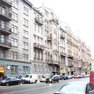 На фото: фасад пятиэтажного кирпичного многоквартирного жилого дома, фасад оштукатурен, эркеры, балконы, перед домом - проезжая часть, тротуар, припаркованные и движущиеся автомобили